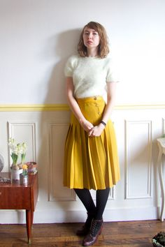 yellow pleated skirt, cream mohair sweater and brown lace up booties.