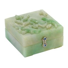 Art Deco Carved Jade, Platinum, Cabochon Sapphire and Diamond Box   The square jade box carved with a bird perched on a blossoming tree, with stylized platinum buckle hinges and clasp set with rose-cut diamonds, centering 6 round cabochon sapphires, circa 192