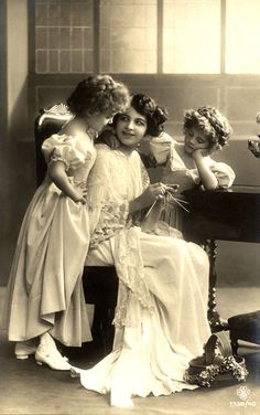 A mother showing her daughters how to knit.