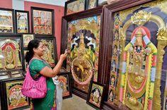 A visitor captures a Thanjavur art piece of Lord Venkateswara through her cell phone at the Poompuhar crafts mela that began in Vijayawada on Tuesday.