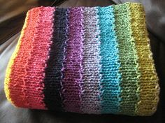 So, so simple. Baby Blanket 11 colors C/O 120 stitches. First colour 6 rows garter for border. Change color with first row k5, k1 p1 across, k5. Knit 5 rows stockinette, the first 5 stitches and last 5 stitches are always knit for the garter border. Change colour and repeat. End with the last colour being 6 rows garter.