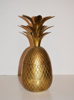 Golden pineapple decor item used in Hollywood Regency style in the 20th century.