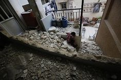 A Palestinian child sits at a house in Qalandia that was demolished by Israeli authorities