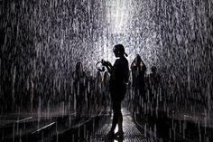 As pessoas visitam o quarto de chuva, uma instalação por artistas aleatória International, em um museu em Xangai, China