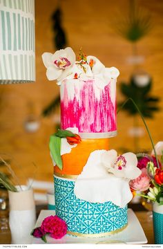 This three-tier wedding cake, boasting an intricate pattern and a fusion of vibrant shades, was decorated with fresh orchids.  | Photographer: Kelly Lemon Photography | Confectioner: Pre'ped by Sasha Catering