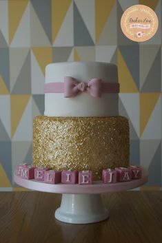Sparkly gold edible sequins and pretty pink bow for this glistening christening cake
