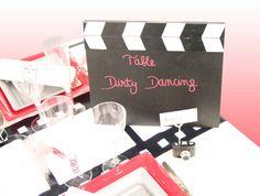 Voici un clap sur lequel nous avons noté le nom de la table. Pour votre mariage, inspirez-vous des plus belles histoires d'amour du 7e art : Dirty Dancing, Pretty Woman, Moulin Rouge, Grease, Titanic, Ghost... Pour un anniversaire, misez sur les grands succès populaires : La Grande Vadrouille, Les Visiteurs, Intouchables, Astérix Mission Cléopâtre, La Guerre des Boutons... Et pourquoi pas Le Dîner de Cons !