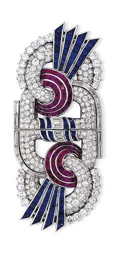 AN ART DECO RUBY, SAPPHIRE AND DIAMOND DOUBLE CLIP BROOCH - Of stylised figure-of-eight design, the openwork bombé frame pavé-set with brilliant-cut diamonds, to the baguette-cut diamond and sapphire centre, further set with opposing calibré-cut ruby and sapphire rosette motif highlights, circa 19