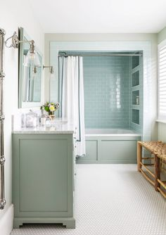Stacked blue subway tiled shower niches in a bathtub alcove add noteworthy character along with blue wainscoting balanced by white hex floor tiles. Blue Bathtub, Bathtub Tile, Bathtub Shower, Bathroom Flooring, Tile Around Bathtub, Bathtub Alcove, Shower Alcove, Tile Shower Niche, Subway Tile Showers