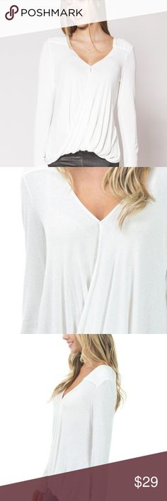 White Surplice Top A gorgeous lightweight surplice top that feels so soft and looks so sweet. This flattering top has a small button in the front that keeps it in place. Pair it with our Pitch Black Leggings for a sleek fall look!  Materials: 95% rayon, 5% spandex Fit: Loose Small is 0-4. Medium is 6-8. Large is 10. Tops