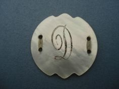 http://www.ebay.fr/itm/VINTAGE-MOTHER-OF-PEARL-BUTTON-INSCRIBED-WITH-D-/251865912082?pt=LH_DefaultDomain_3