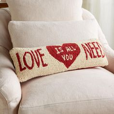 """LOVE IS ALL YOU NEED BOLSTER--Send a message on Valentine's or any day with our sentimental pillow, designed by Vermont artist Laura Megroz and hand hooked in New Zealand wool. Zippered red cotton velveteen back, polyester fiberfill insert. Imported. Exclusive. 24""""W x 8""""H."""