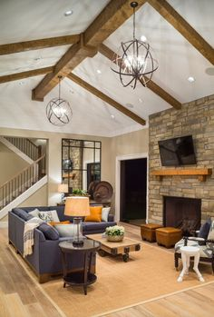 Cozy, contemporary rustic family room: Stone fireplace, vaulted ceiling with exposed beams, rustic coffee table, contemporary sectional sofa, contemporary chandeliers