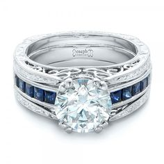 #102340 This stunning engagement ring features a round brilliant cut diamond accented with princess cut blue sapphires, all set in an ornate platinum band....