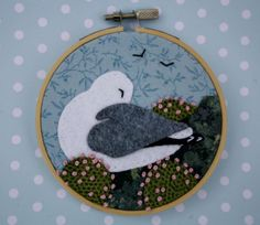 A hand-embroidered coastal scene. A gull sleeps among clumps of sea-pinks on the rocky cliffs.  I created this scene by applying fabric scraps in