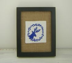 Hand stitched embroidery. Dark blue stag head with wreath cross stitch mounted onto a natural untreated linen fabric Framed in a thick black wood frame with a glass front which can be placed onto a flat surface  using the stand or hung onto the wall. Size approximately 9 and 1/4 inches x 7 and 1/4 inches (23.5cm x 18.5cm). One of a kind