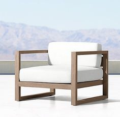 Patio Chair - RH Ours is black aluminum instead of teak, with the same white woven cushions.
