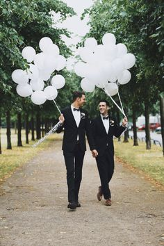 Gay wedding photo of the two grooms, walking with white balloons. Surrounded by nature #gaywedding #wedding #groom #grooms #balloons