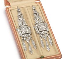 A pair of Art Deco diamond pendent earrings, by Cartier, circa 1925 Each elongated plaque, composed of articulated geometric motifs, pierced and set throughout with old brilliant and single-cut diamonds, terminating in a similarly-set diamond tassel, diamonds approximately 8.20 carats total, each signed Cartier