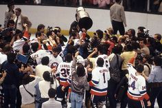 Denis Potvin of the New York Islanders hoists the Stanley Cup after the Islanders defeated the Edmonton Oilers in Game Four of the 1983 Stanley Cup Finals to sweep the seven-game series at Nassau Coliseum on May 1983 in Uniondale, New Y Stanley Cup Finals, Stanley Cup Champions, Denis Potvin, Hockey, Bruce Bennett, Nassau Coliseum, New York Islanders, Edmonton Oilers, Those Were The Days