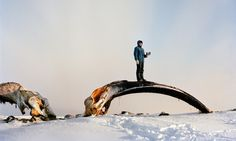 In Repulse Bay, Canada, a man stands on a giant whalebone in one of a collection of portraits taken within 35 miles of the Arctic circle. The images, taken over 13 trips to eight countries, are from a book called Life on the Line Christian Barnett
