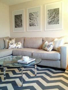 Sweet White Wooden Frames Artwork Portray At White Wall Painted Over Cool L-shaped Grey Fabric Sectional Sofas With Cute White Cushions As Well As Smart Round Glass Coffee Table Over Chic Chevron Rug Black And White Striped Color For Decorate Modern Living Room Design Views