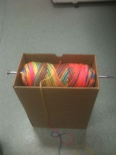 Ingenious way to hold your yarn while crocheting. Box, one large knitting needle, and yarn!!  The best way to use a knitting needle!