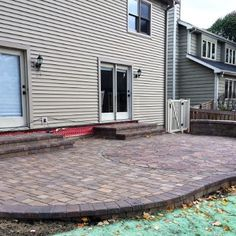 This patio was created using Belgard Cambridge cobble pavers in Danville Beige. The Mega Arbel inset circle in Ashbury Haze creates definition by creating two different areas -one which can be used for seating and the other for perhaps grilling or a future Chicago outdoor kitchen. The Weston seat wall creates separation from the rest of the yard. This paver patio was custom designed and built by Wheaton, IL patio builder Archadeck of Chicagoland.