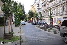 """Berlin. Śródmiejska zabudowa z końca XIX w. W środku ulicy widoczna """"szykana"""" zmuszająca kierowców do zwolnienia."""