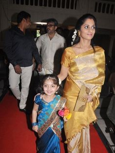 Shalini Ajith kumar in traditional gold colour silk saree with gold border paired with matching gold short sleeves saree blouse. Shalini's daughter baby Anoushka is lovely in blue half saree(patu langa) at mirchi siva's wedding.