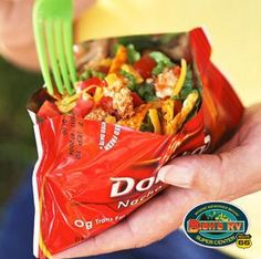 Camping recipe for tacos in bags. small bags Dorito chips per person, 1/2 cup cooked and Taco-seasoned hamburger, shredded or chopped lettuce, shredded cheddar or Mexican-mix cheese, diced onions, diced tomatoes, salsa or taco sauce, and plastic forks or spoons. Add ingredients wanted, fold top of bag closed and shake to mix up. That's it.