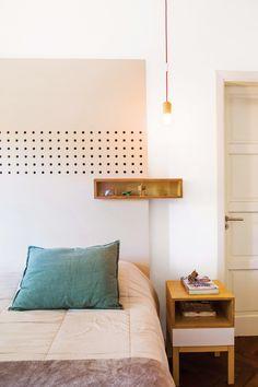 Dormitorio matrimonial moderno con gran cabecera de madera que incluye un estante exhibidor y mesita de luz de guatambú.