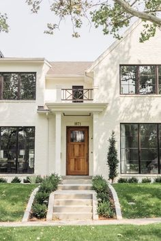 Best exteriors of 2017. Classic + Modern off white painted brick house with wood door and black windows! Click to see the full home tour