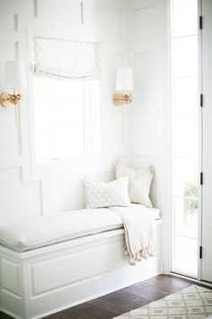 Gorgeous white foyer features a white built-in wainscoted bench fixed against a white wall accented with a white decorative trim mounted framing a window dressed in a light gray roman shade flanked by Worlds Away Delilah Wall Sconces.