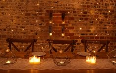 Pealight cascade as top table backdrop, crossback chairs and rustic trestle tables, lace table runner with brass terrarium lanterns for a rustic barn wedding at Upwaltham Barns by www.stressfreehire.com #venuetransformers