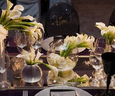 Mix the shape and material of your vessels and add a mirrored tabletop for a chic centerpiece full of white Calla lilies.