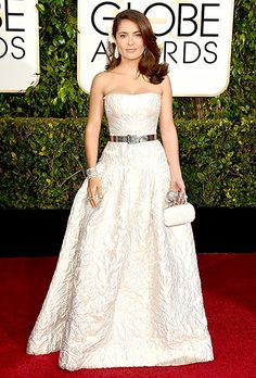 Salma Hayek Hayek stood tall in a white brocade dress by Alexander McQueen, cinched at the waist with a silver belt. Feather-shaped diamond earrings and roses in her hair completed the ensemble
