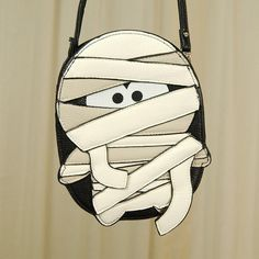 This white, tan and black mummy crossbody bag is the perfect accessory for Halloween or everyday! The interior is lined in black fabric, has a slot pocket on either side, has a 54 inch black vinyl strap is adjustable and detachable, and ...