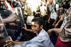 A Syrian boy pushed againsta a police barricade as Syrian refugees marched along a highway that had been temporarily opened to the border at Erdine, Greece, AFP