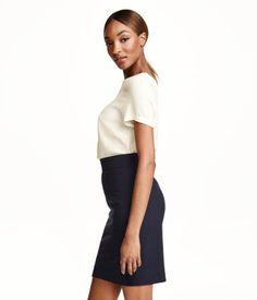 Fitted skirt in woven stretch fabric. Wide waistband, welt back pockets, and concealed zip and slit at back. Lined.