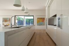 Morcon Developments - Lansell Road Toorak white Kitchen with different size caravaggio pendants