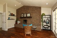 The sitting room area, leads out to the rear yard and has a floor to ceiling stone fireplace too. The left side has a corner that would be great for a desk or office nook. The right side has plenty of room for books or shelving too!