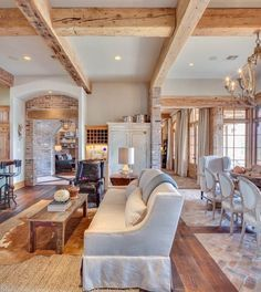 Rough hewn, bleached beams create coffered ceiling; brick paver, reclaimed wood floors, arched doorways, and neutral decor in an open concept give us so much to love here.