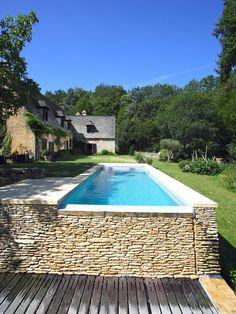 L'esprit nature par l'esprit piscine . 9 x 3 m . Revêtement gris clair . Margelles en pierre naturelle de Vèze . Mur de débordement en lauze .