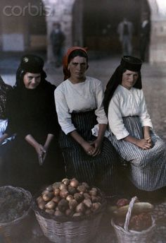 Three portuguese women pose with their baskets of goods at the market