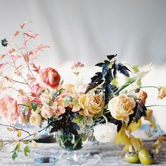 What a stunner. The dark leaves add such a bold touch of drama to this centerpiece. #flowers #wedding