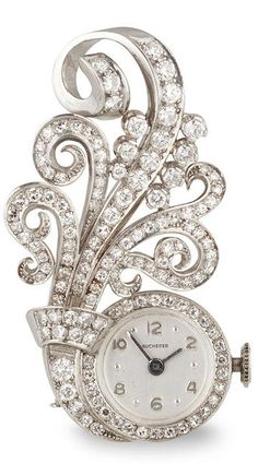 *A diamond watch brooch of scroll design, set throughout with single-cut diamonds; dial signed Bucherer; estimated total diamond weight: 1.10 carats; mounted in platinum; length: 1 3/4in