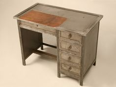 This authentic vintage French jewelery maker's desk is one of those unique items that does not require a second glance to know it is something special. Offering sturdy solid wood construction covered with industrial steel, it is in nice, original used condition (see stained spots in detailed photos) with 4 smooth functioning side drawers with pierced brass leaf-form pulls, and a steel caged front for added stability and to allow for air circulation.