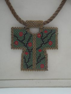 A beautiful peyote Caftan pendant! Made of Miyuki in dark brown, green, black, and red Miyuki chain necklace but it can be removed and worn with another