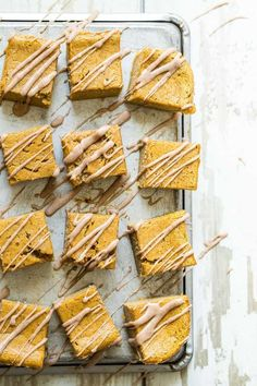 Creamy Pumpkin Magic Cake topped with a pumpkin spice frosting drizzle. This is a great make-ahead dessert for the holidays!